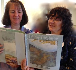 Author Melissa Stewart (left) and I thumb through her book about animal adaptation in winter, Under the Snow (illustrated by Constance R. Bergum), at the Massachusetts Environmental Education Society conference, Spring 2014.