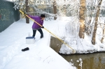 A woman uses a long pole reaching from a bridge into the water on a snowy day.