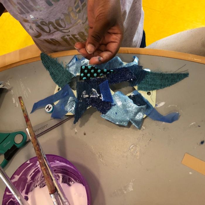 bowl-of-glue-with-child;s-hand-using-fabric-scraps-all-different-textures-shades-of-blue