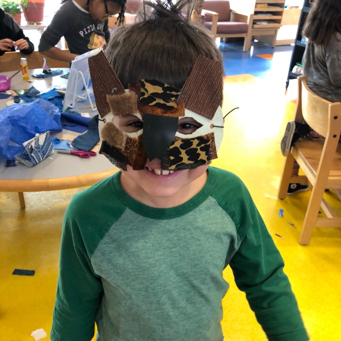 boy-in-green-shirt-wearing-owl-mask-made-of-collage-fabric